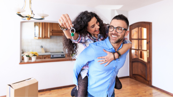 young couple holding keys to new home