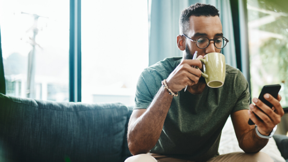 Man drinking coffee and looking at his phone