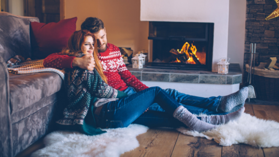 Young couple sitting by a fireplace